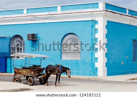 carriage with horse over blue old building, Cienfuegos, Cuba - stock photo