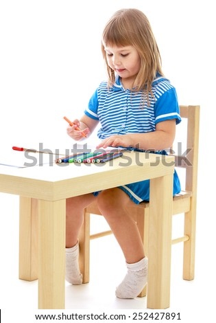 Carried away by a little girl draws a table markers.Isolated on white. - stock photo