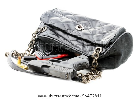 Carried concealed. Handgun and accessories falling from a woman's purse. Isolated on white with light shadow. - stock photo