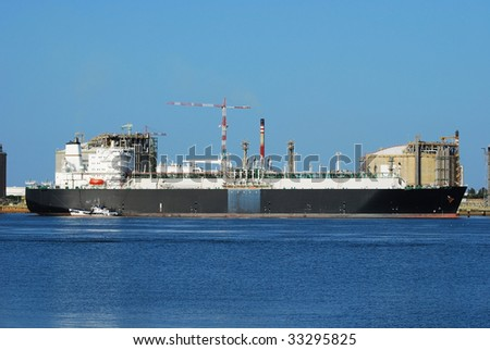 Carrier ship (LNG) and oil i gas factory in Spain - stock photo