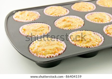 Carrot and apple muffin batter in a non-stick muffin tin. - stock photo