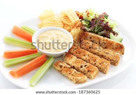 carrot and celery batons with humus dip - stock photo