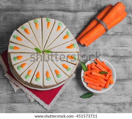 Carrot Cake Pie, sprinkled with nuts, decorated with cream-colored carrots on stand for cakes, fresh whole carrots, sliced sticks carrots on light white background wooden, top view - stock photo