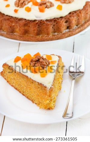 Carrot cake with icing and fork on white plate - stock photo