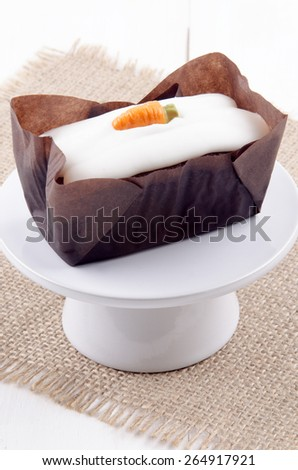 carrot cake with icing on a small cake stand - stock photo