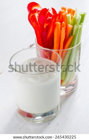 Carrot, celery, pepper sticks in glass, yogurt sauce, white wood background - stock photo