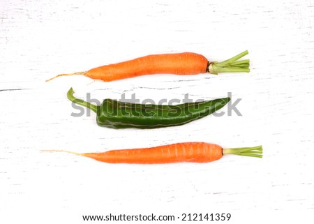 Carrot isolated on white with green sweet pepper background