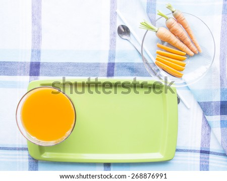 Carrot juice diet food on waiter with ingredient on blue table mat - stock photo