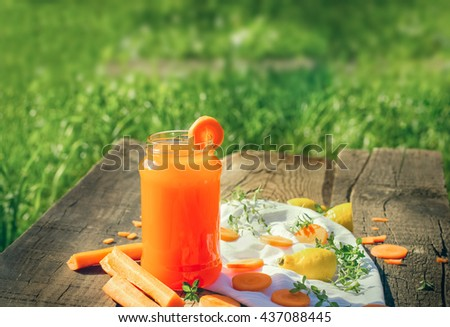 Carrot juice in jar - refreshing drink on rustic table - stock photo