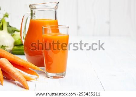 carrot juice on white wood  background  - stock photo