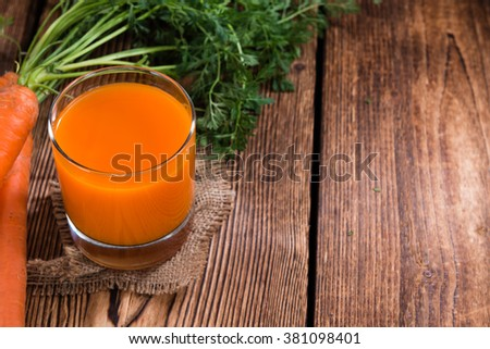 Carrot Juice (selective focus) as close-up shot on wooden background - stock photo