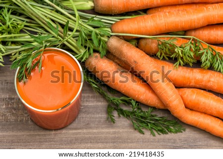 Carrot juice with fresh vegetables on wooden background. Healthy food and drinks - stock photo