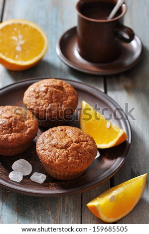 Carrot muffins with fresh oranges fruit on wooden background - stock photo