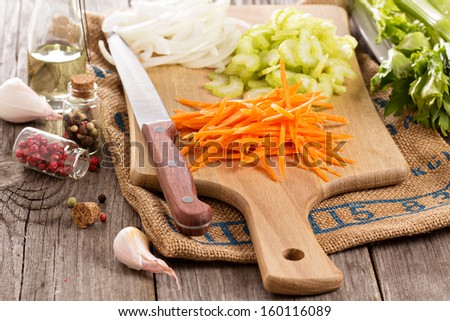 Carrot, onion and celery on a cutting board - stock photo
