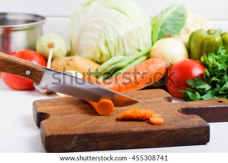carrot slices and fresh and healthy mixed raw vegetables, soup ingredients and other food products in a wicker white wooden table in the kitchen,selective focus - stock photo