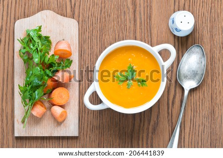 Carrot soup close up with fresh carrot, parsley, spoon and salt shaker - stock photo