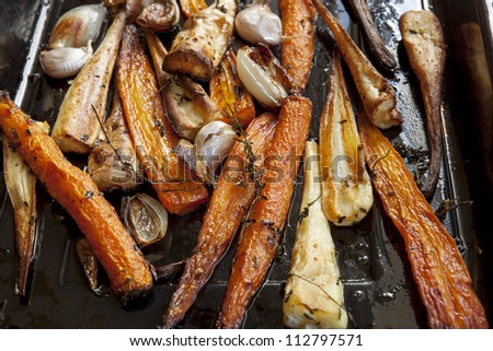 Carrots and parsnips roasting in a pan, with thyme, shallots, and garlic. - stock photo