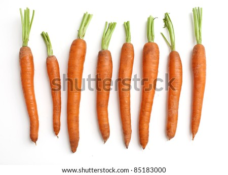carrots arranged by size on white background - stock photo