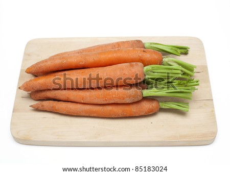 carrots on cutting board over white - stock photo