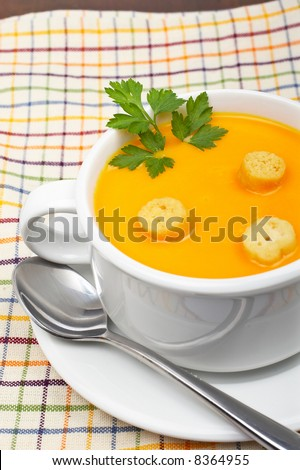 Carrots puree with bread croutons and parsley, on white cup over squared mat. Shallow DOF