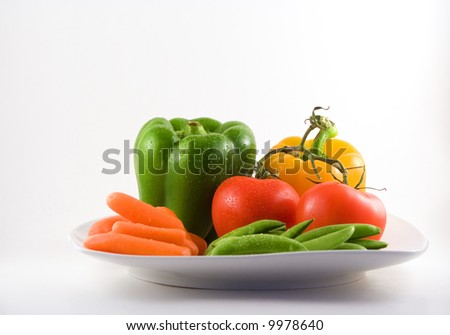 Carrots, tomatoes, green peas and two bell peppers on a white plate. - stock photo