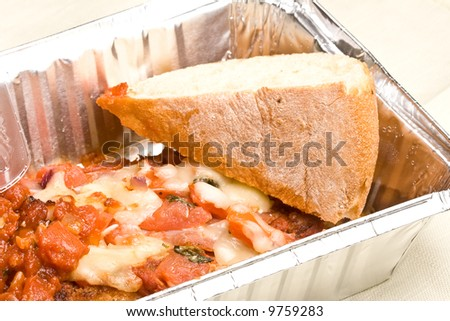 carry out meal chicken parmesan with a slice of bread in the carry out container - stock photo
