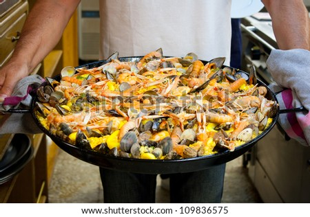 Carrying a freshly made seafood paella cooked in a basque gastronomic society in San Sebastian - stock photo