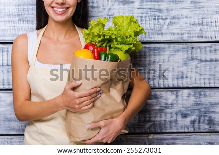 Carrying a healthy bag. Cropped image of beautiful young woman in apron holding paper shopping bag full of fresh vegetables and smiling while standing in front of wooden background - stock photo