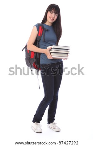Carrying education books a beautiful smiling young Japanese teenager high school student girl wearing blue denim jeans and t shirt, backpack over her shoulder. - stock photo