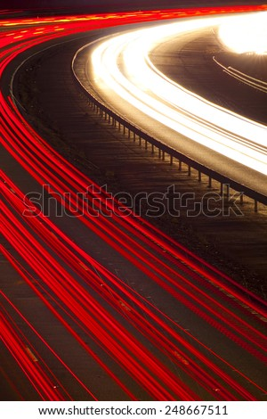 Cars and lorries leave ghostly light trails as they pass by quickly on this night road - stock photo