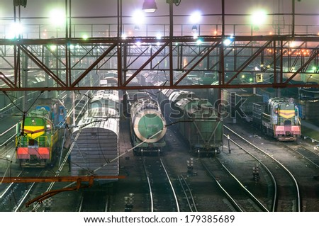 Cars and trains staying on rails at night time in depot - stock photo