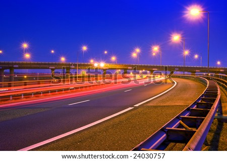 Cars breaking on an overpass of a motorway at night - stock photo