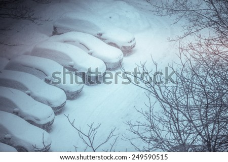 Cars covered in snow on a parking lot in the residential area during snowfall. Filtered shot  - stock photo