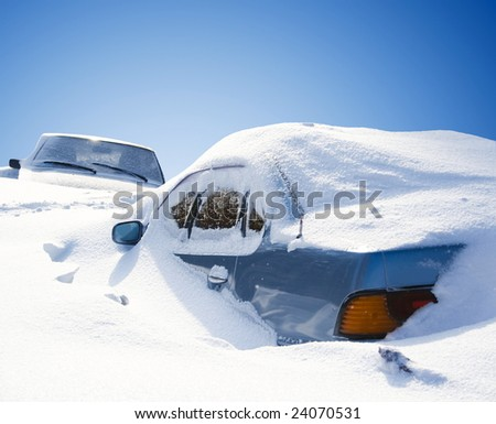 cars covered with snow in the winter blizzard - stock photo
