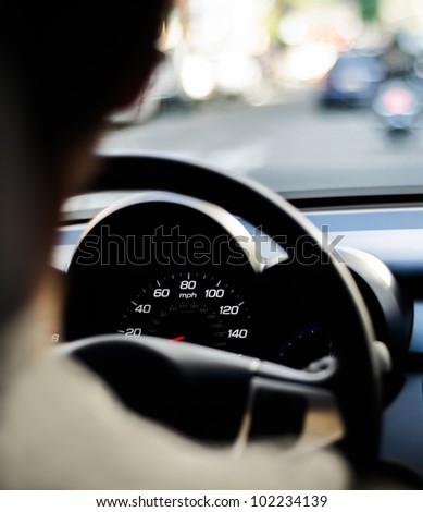 Cars dashboard view over a drivers shoulder - stock photo