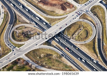 Cars drive along a vast, curving road below. - stock photo