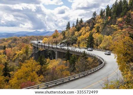 Cars drive over Linn Cove Viaduct, Blue Ridge Parkway in the Fall, NC - stock photo