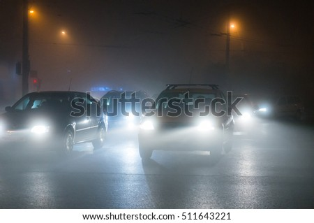 Cars driving in the fog at night.