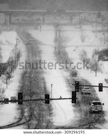 Cars driving in winter blizzard snow storm on streets in town with traffic lights - stock photo