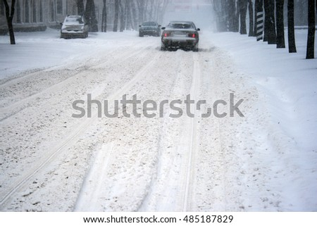Cars driving on slippery road during heavy snowfall