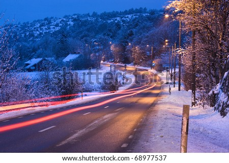 Cars driving on small road in winter landscape - stock photo
