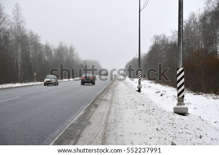 cars driving on winter asphalt road - slippery road