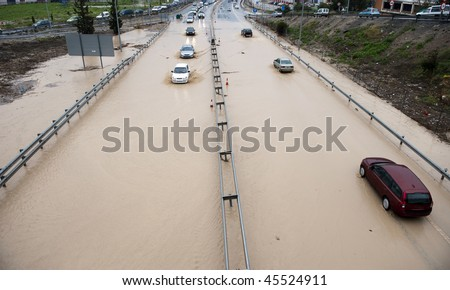 Cars going through flood highway and huge traffic jam (no trademarks) - stock photo