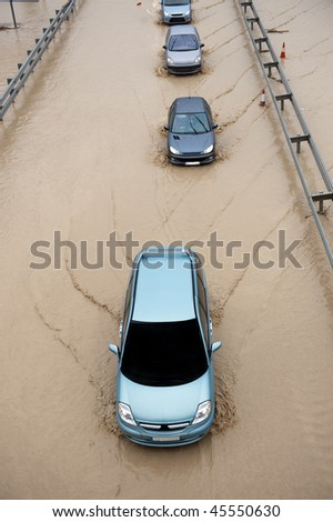 Cars going throught flood highway - stock photo