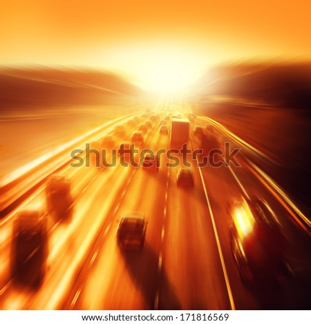 Cars in motion blur on highway during sunset. - stock photo
