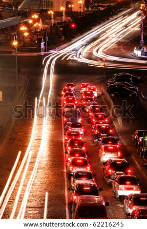 Cars in the movement and standing on the crossroads in the night city - stock photo