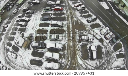 Cars in the parking lot covered with snow, aerial view - stock photo