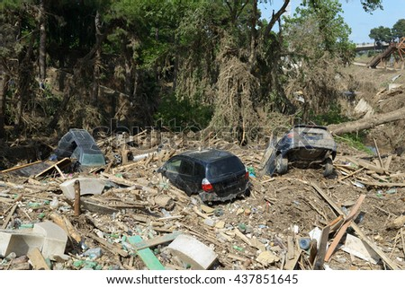 cars lay in the debris after the flood disaster - stock photo