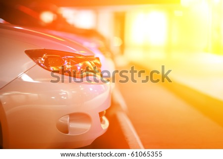 Cars lined up in parking lot. Closeup, shallow DOF. - stock photo
