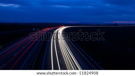 Cars moving fast on a highway - stock photo